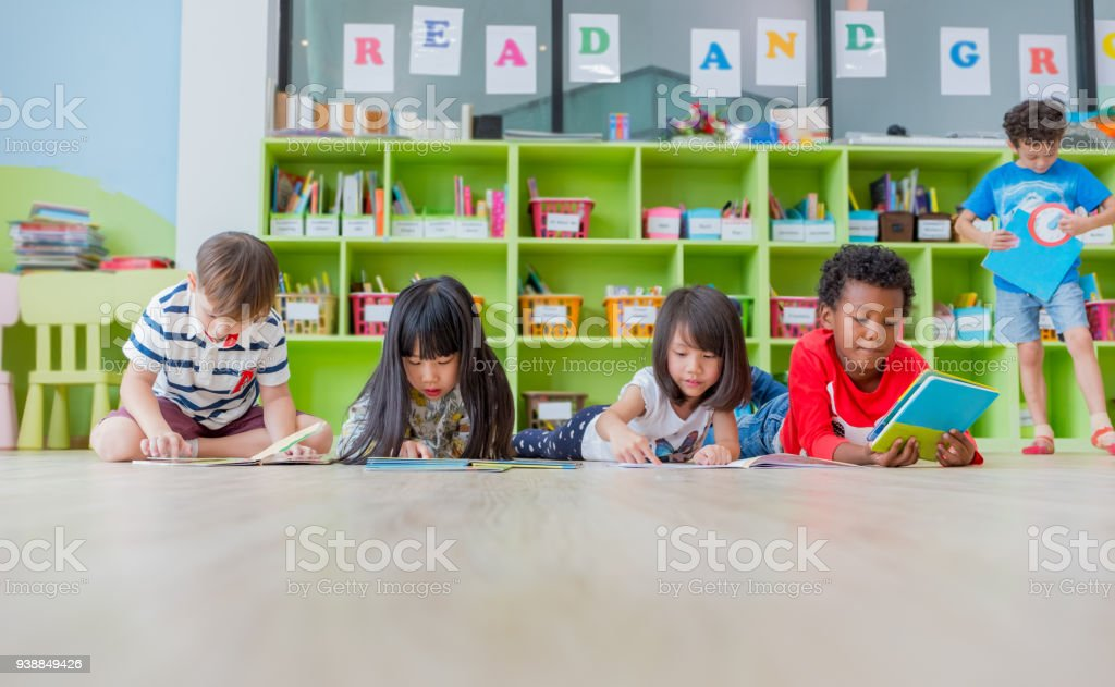 Group of diversity kid lay down on floor and reading tale book in preschool library,Kindergarten school education concept stock photo