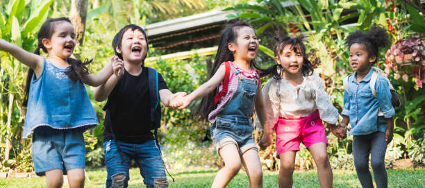 Group of diversity kids holding hands and playing at outdoor park with happy and funny stock photo