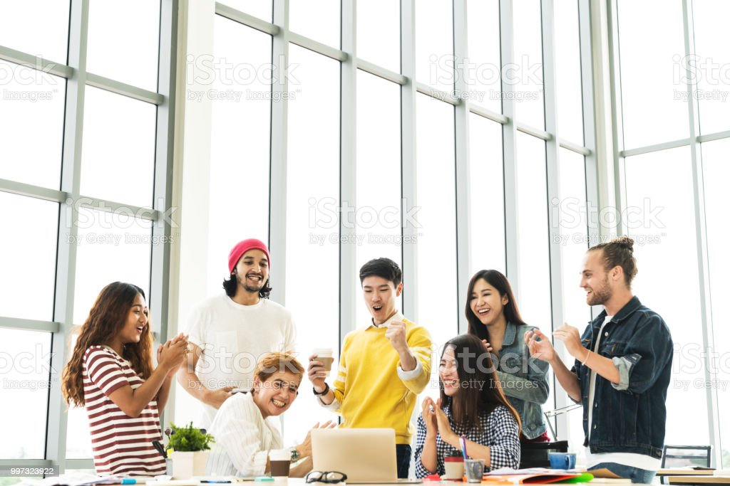Group of Diversity People Team smiling and cheerful in success work with laptop at modern office. Creative Multiethnic or Ethnicity teamwork feeling happy, enjoy and engaged with achievement project. stock photo