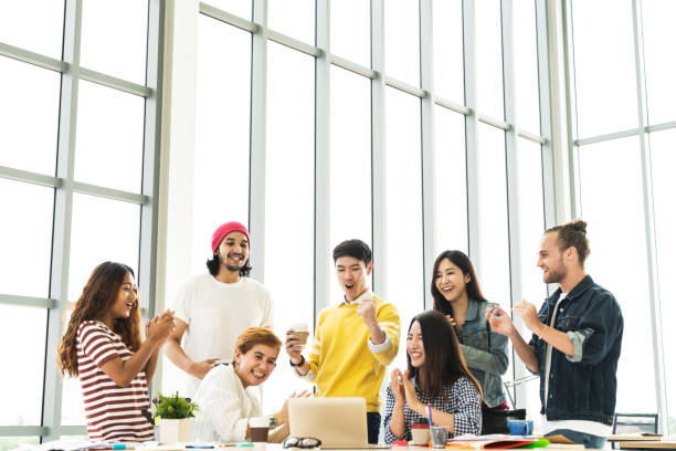 group of diversity people team smiling and cheerful in success work with laptop at modern office. creative multiethnic or ethnicity teamwork feeling happy, enjoy and engaged with achievement project. - employee engagement stock photos and pictures