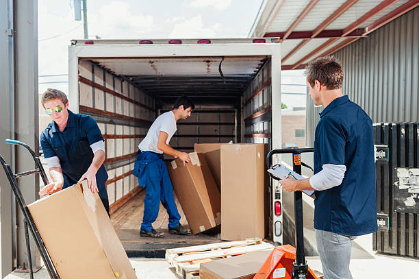 A group of dock workers are loading a delivery truck stock photo