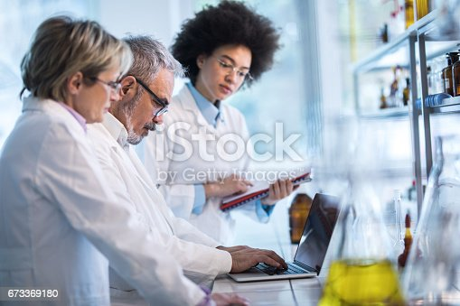 Three scientists working in a laboratory. Focus is on mature man typing on laptop.