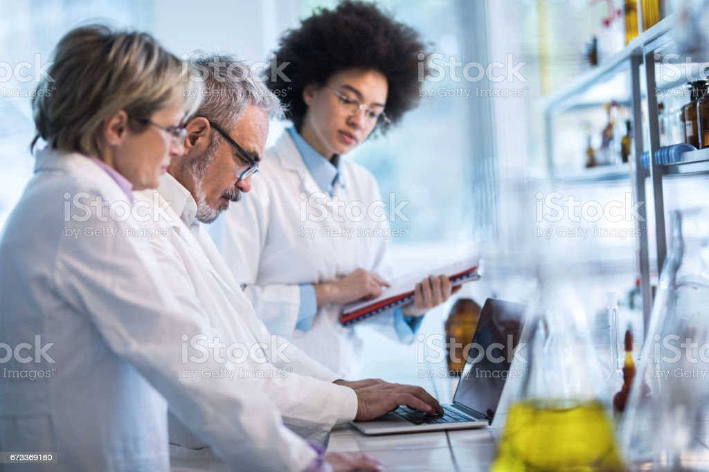 Group of doctors analyzing medical data on laptop in the laboratory. stock photo