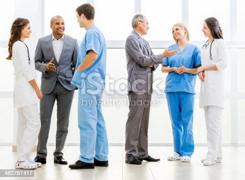Group of doctors and two businessmen standing in a corridor and discussing.