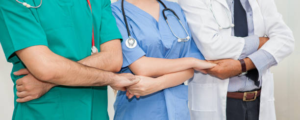 group of doctors and nurses holding hands together in a medical team . Cooperation stock photo