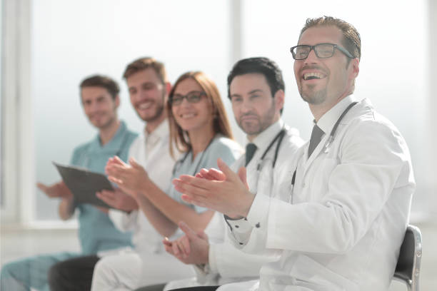 A group of doctors applauding the side view stock photo