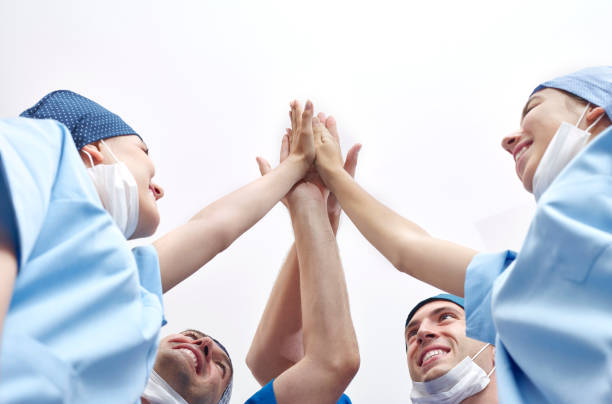 Group of doctors doing high-five stock photo