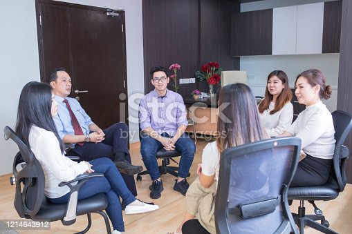 944493796 istock photo A group of doctors having discussion with smiling face in doctor's office at hospital 1214643912