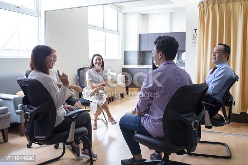 944493796 istock photo A group of doctors having discussion with smiling face in doctor's office at hospital 1214644690