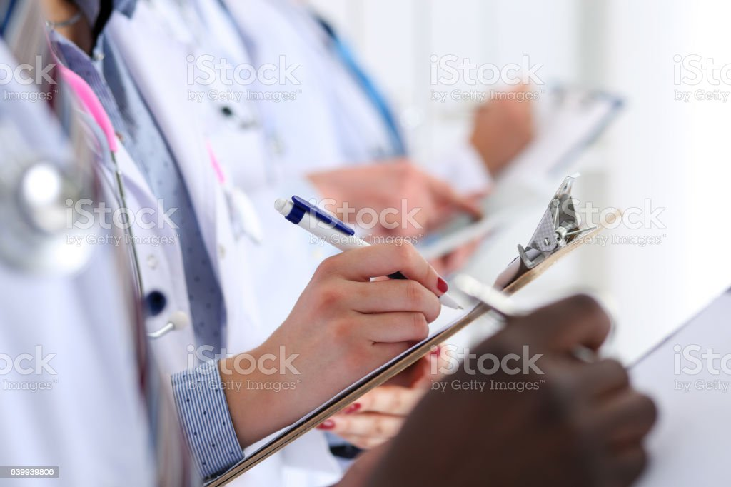 Group of doctors hold pens and clipboard pads stock photo