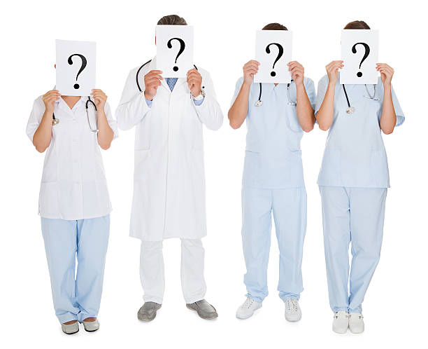 group of doctors holding question mark sign - question mark asking doctor nurse stock photos and pictures