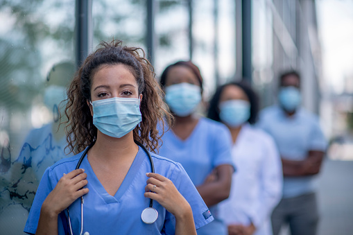 Diverse group of medical professionals outside the hospital wearing protective face masks.