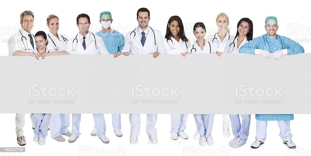 Grupo de médicos apresentando faixa vazia - foto de acervo