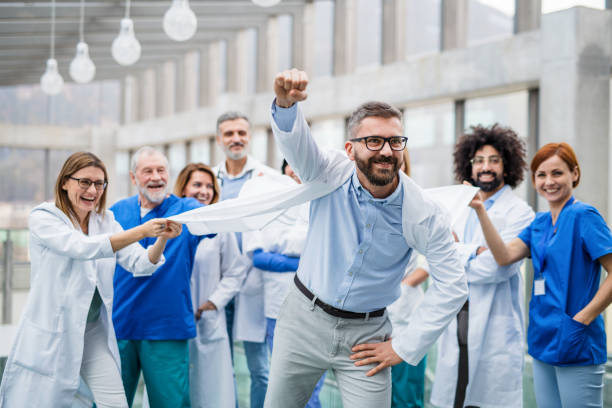 Group of doctors standing in corridor on medical conference, having fun. stock photo