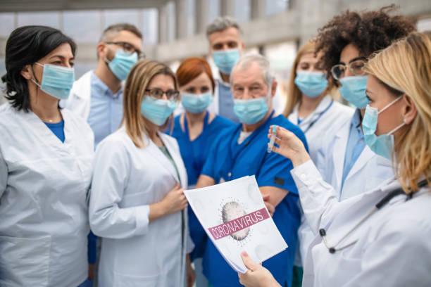 groupe de médecins parlant du virus de couronne sur la conférence. - medecin covid photos et images de collection