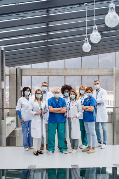 Group of doctors with face masks looking at camera, corona virus concept. stock photo
