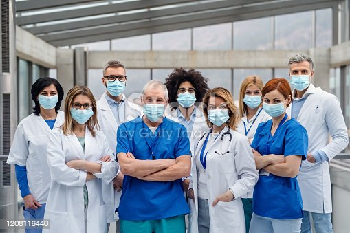 istock Group of doctors with face masks looking at camera, corona virus concept. 1208116440