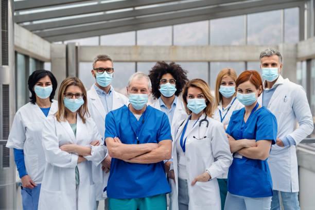 カメラを見てフェイスマスクを持つ医師のグループ, コロナウイルスの概念. - マスク ストックフォトと画像