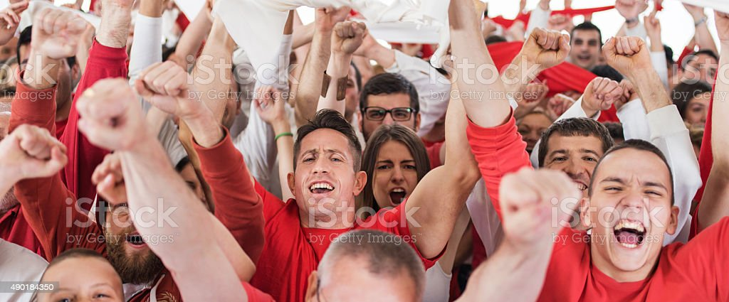 Large group of ecstatic fans celebrating with their arms raised. They...