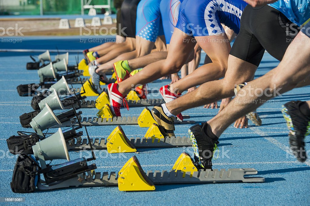 Group of eight athletes starting 100m sprint royalty-free stock photo