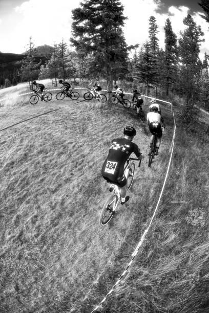 eine gruppe von acht männern konkurrieren in einem querfeldein-radrennen. - cyclocross stock-fotos und bilder