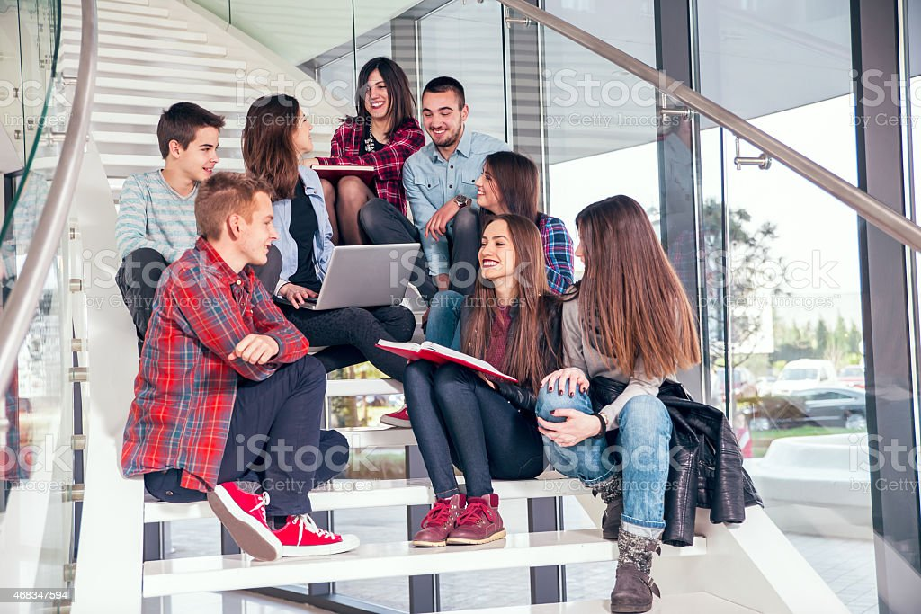 Group of eight students studying on school's stairs royalty-free stock photo