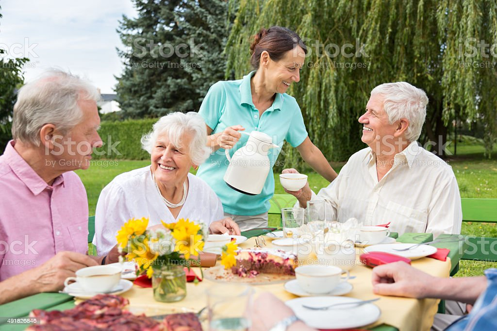 Group of elderly people sitting at the garden table and celebrating...