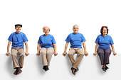 istock Group of elderly people wearing blue t-shirts sitting on a white panel and smiling at the camera 1174509167