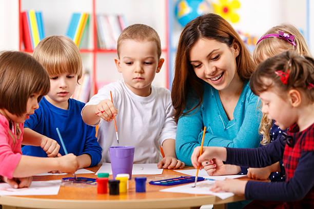 elementary age (小学校低学年)のお子様のグループでのクラスの美術教師 - 美術の授業 ストックフォトと画像