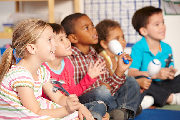 group of elementary age schoolchildren in music class - preschool child stock photos and pictures