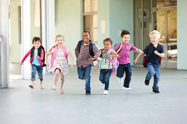 group of elementary age schoolchildren running outside - school building stock photos and pictures