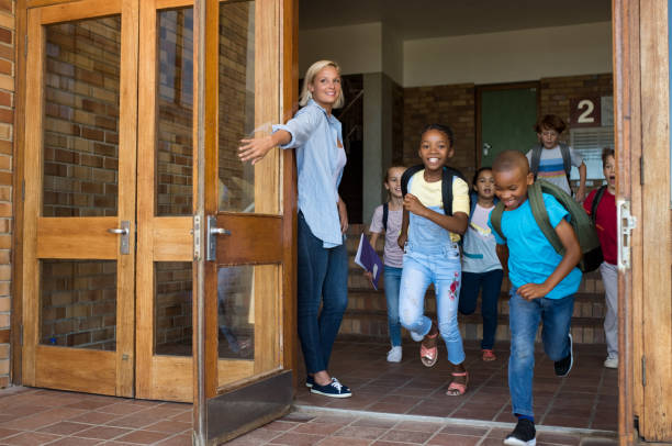 group of elementary children running outside school - school building stock photos and pictures