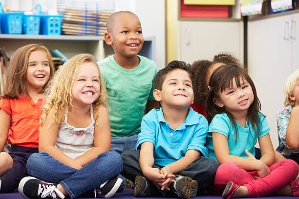 Group of elementary pupils having fun in classroom stock photo