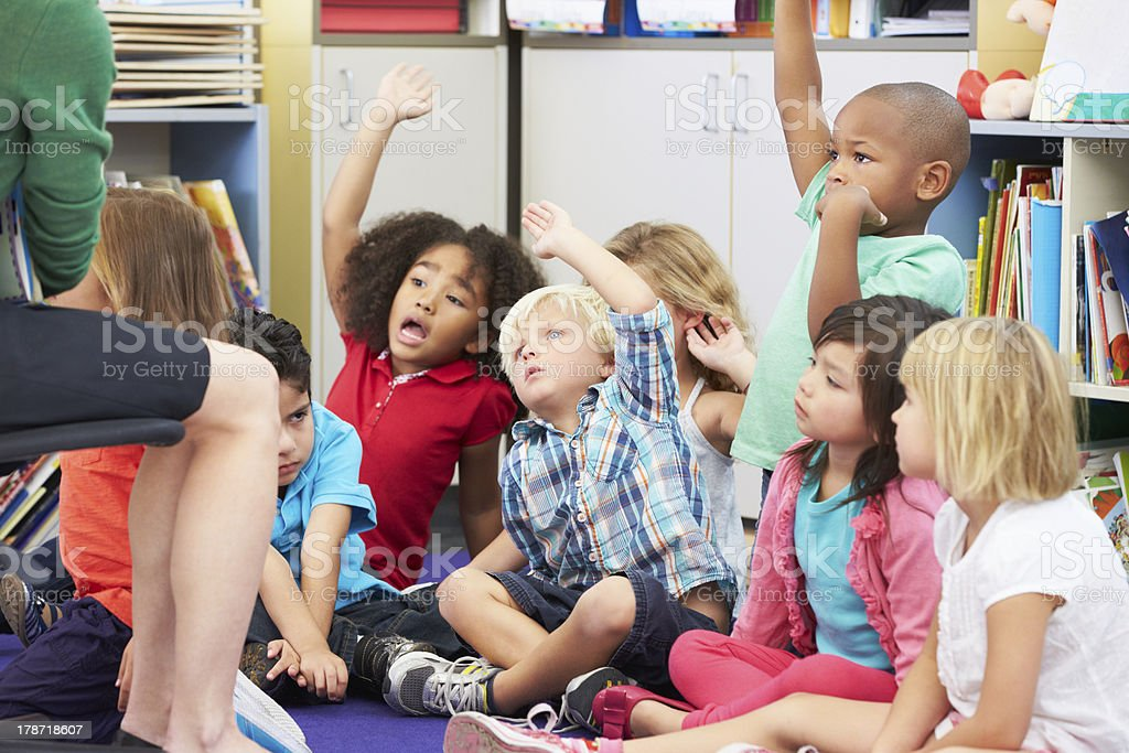 Group of Elementary Pupils In Classroom Answering Question stock photo
