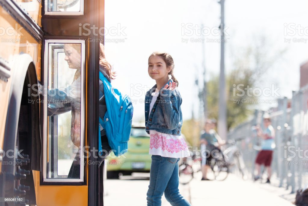 Group of elementary school kids getting in a school bus at school's out. royalty-free stock photo