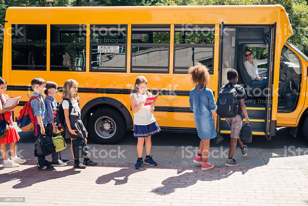 Group of elementary school kids getting in yellow school bus. - foto de stock