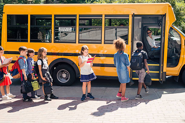 group of elementary school kids getting in yellow school bus. - school bus stock photos and pictures