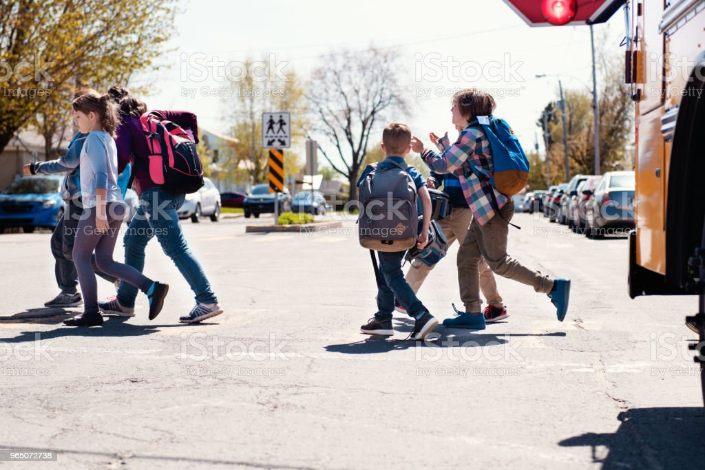 Group of elementary school kids getting out a school bus at school's out. royalty-free stock photo