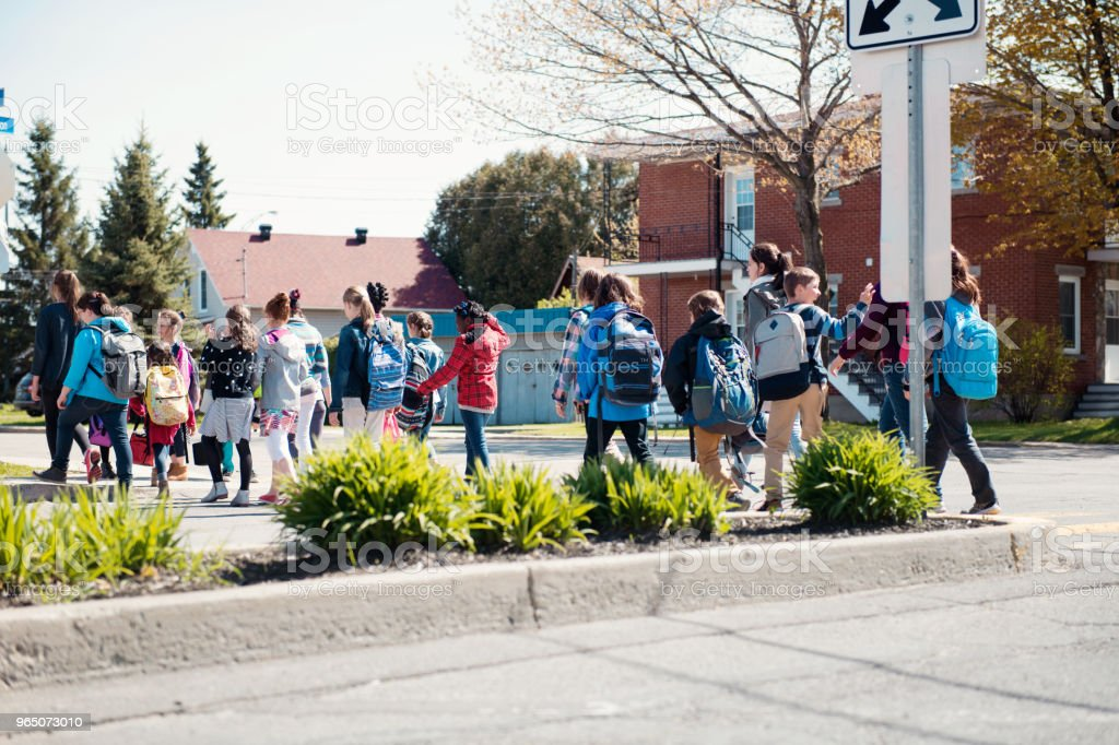 Group of elementary school kids getting out a school bus at school's out. zbiór zdjęć royalty-free