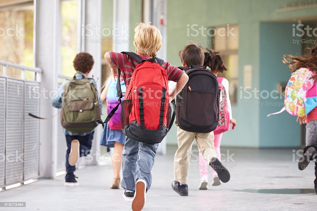 Group of elementary school kids running at school, back view stock photo