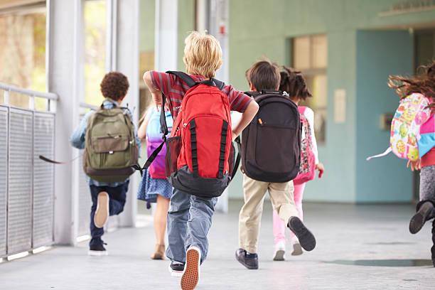 小学校のお子様のグループランニングで学校、バックの眺め ストックフォト