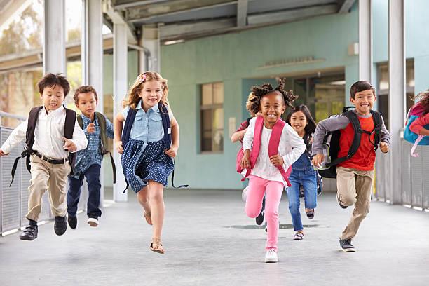 grupo de niños de escuela primaria corriendo en una escuela corredor - patio de colegio fotografías e imágenes de stock