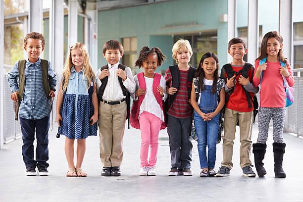 Group of elementary school kids standing in school corridor stock photo