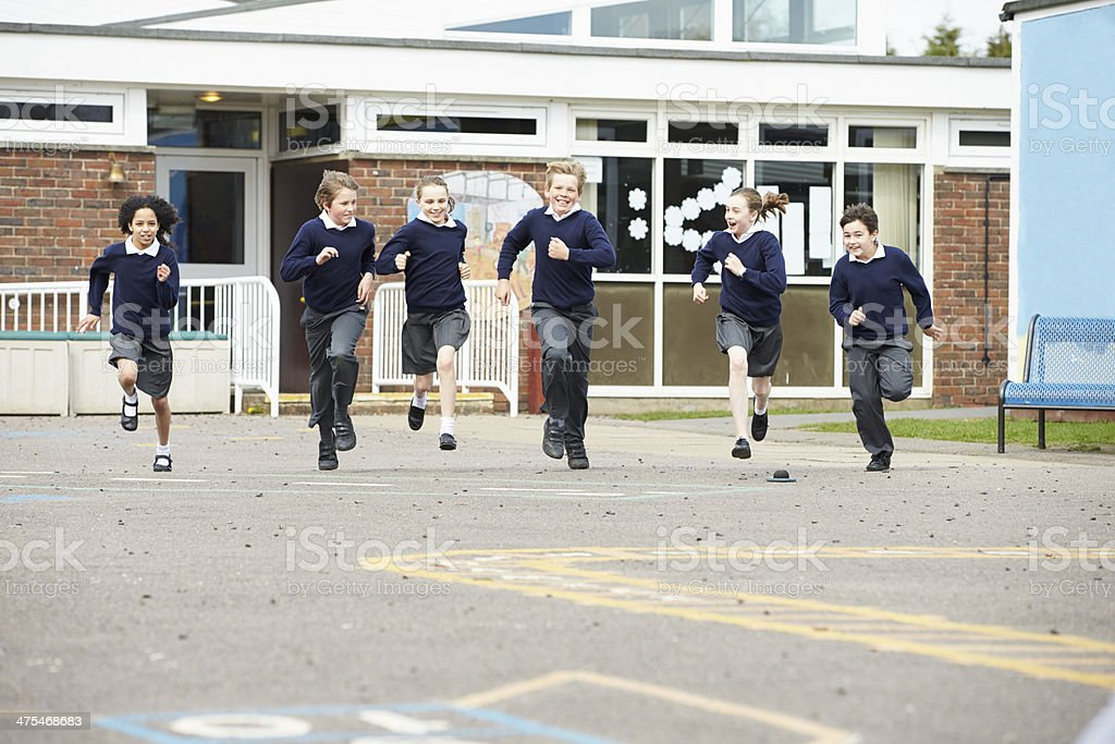 Group Of Elementary School Pupils Running In Playground royalty-free stock photo
