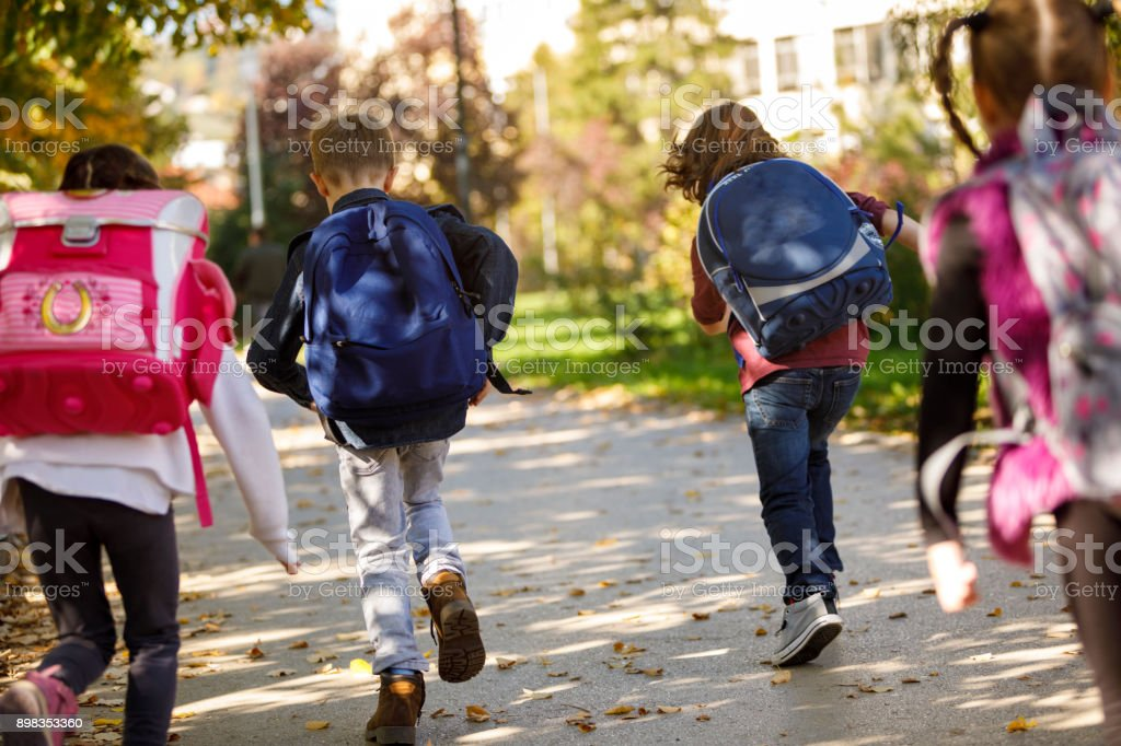Group of elementary school pupils running outside stock photo