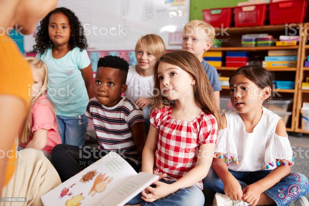 Groep basis school leerlingen zittend op de vloer luisteren naar vrouwelijke leraar Lees verhaal - Royalty-free 20-29 jaar Stockfoto
