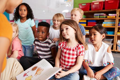 Groep Basis School Leerlingen Zittend Op De Vloer Luisteren Naar Vrouwelijke Leraar Lees Verhaal Stockfoto en meer beelden van 20-29 jaar