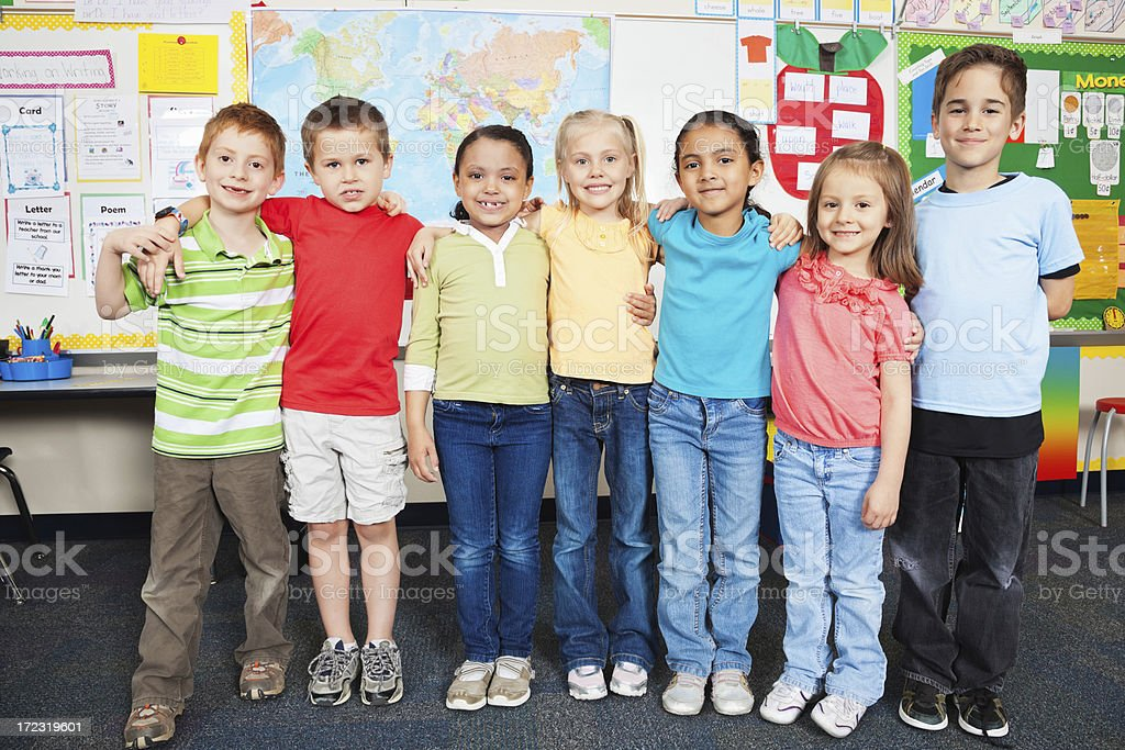 Group of elementary school students posing together in classroom royalty-free stock photo
