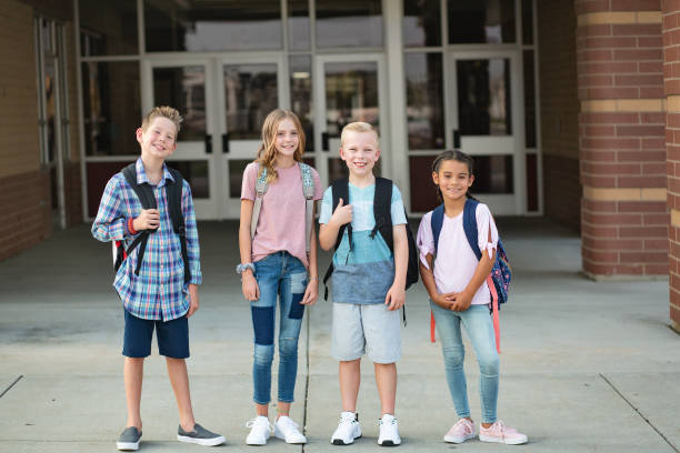 Group of Elementary school students standing in front of their school. Smiling and hanging out together after school. stock photo
