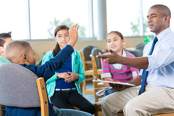 Group of elementary students in tharapy or counseling session Diverse group of elementary age little boys and little girls are sitting in a circle in school library or therapist's office. Students are attending group therapy or counseling session. Mid adult African American man is counselor or therapist. He is pointing to child whose hand is raised to ask a question. school counselor stock pictures, royalty-free photos & images